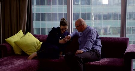 rich family of freelancers at home in a luxury apartment in the center of a modern city sitting on the couch watching the news on the phone Reklamní fotografie