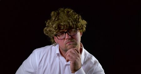 Portrait of a curly-haired man with glasses on a black background. Sad and gesticulating when thinking