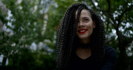 A close-up portrait of a searing brunette with curly hair, red lipstick on her face, piercings in her nose and above her lip. She is in nature, looking up, posing, smiling.