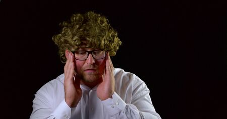 A close-up portrait of a curly-haired man in glasses and a white shirt, he is on a black background in the Studio grabbing his head, rolling his eyes, frightened and clasping his hands. 写真素材