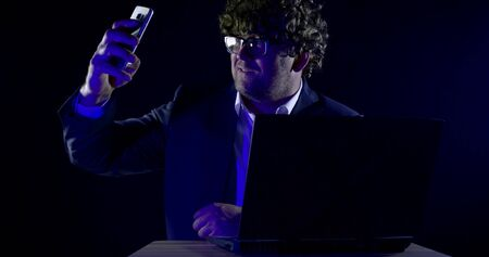 Close-up portrait of a curly-haired man in glasses and a shirt, jacket he sits at a laptop on a black background, taking a selfie on the phone, smiling.