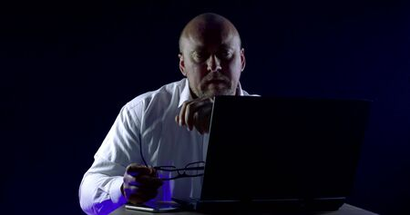 Close-up portrait of a bald man in glasses and a shirt, he is sitting at a laptop, emotions, happy looking at the computer screen, rooting for someone, next to him on the table is a mobile phone. Фото со стока