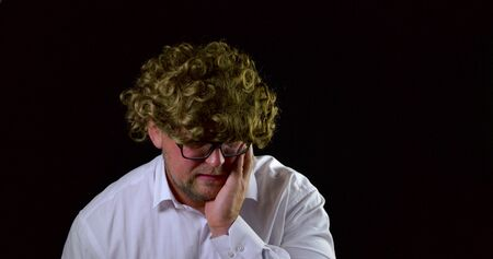 sorrowful man with curly wig is sitting in black background, touching face by hand 写真素材