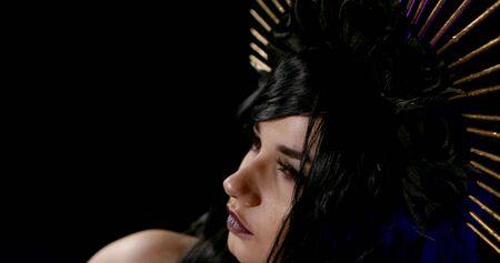 Ritratto ravvicinato di una ragazza in maschera come la Vergine Maria su sfondo nero