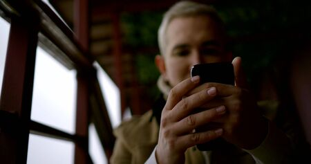 man is checking email in smartphone, closeup of hands, portrait is blurred