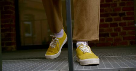 young man is walking on outdoor balcony, closeup view of his trendy yellow shoes Zdjęcie Seryjne