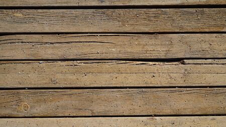 Background texture of old wooden boards decking on sand
