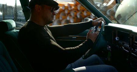 männlicher Fahrer sitzt auf dem Fahrersitz und tippt Nachrichten und liest Nachrichten im Smartphone