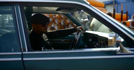 alone man with cap on head and sunglasses is sitting in car in sunny day Archivio Fotografico