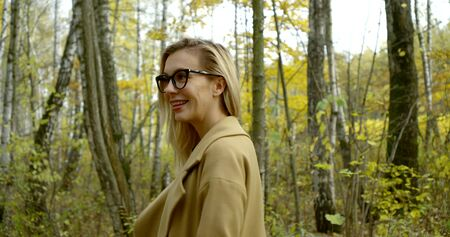young woman with braces on teeth and glasses on face is standing in forest in fall day, smiling and turning Zdjęcie Seryjne