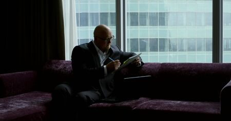 A bald businessman in a business suit and glasses, he sits in the room at the panoramic window on a purple sofa, on his knees he has a laptop, he holds a notebook with a pen, writes.