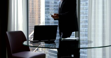 a businessman in a business suit, he stands in the office at the panoramic window in which you can see the skyscrapers near the round glass table on which there is a laptop, he is holding a phone.