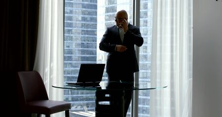 A bald businessman in a business suit and glasses, he stands in the office at the panoramic window in which the skyscrapers are visible near the round glass table on which there is a laptop, talking on the phone.