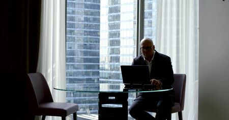 A bald businessman in a business suit and glasses, he sits in the office at a round glass table on which there is a laptop, works at it, then loses his phone from his pocket. In the background in the panoramic window of the skyscraper.