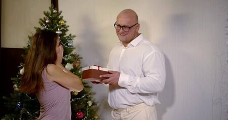 A bald Husband in glasses, in a white shirt gives a dark-haired happy wife in a dress a gift in a box, they are at home against the background of a Christmas tree with balls and garlands, kissing. Zdjęcie Seryjne