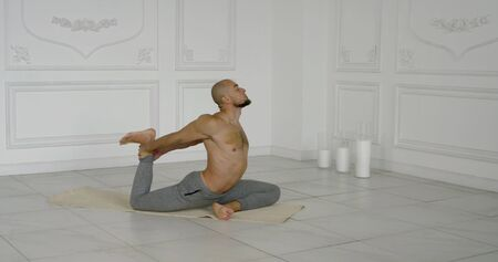 Flexible and plastic male yogi with a beard doing yoga on a rug in a bright Studio. He pulls the front of his thigh. Zdjęcie Seryjne