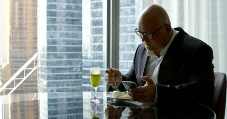 businessman in a suit, he sits in his offices panoramic window in which you can see high-rise buildings, round glass table in front of him is a plate and a glass. He eats and looks at the phone.