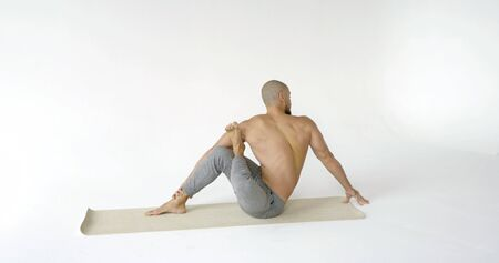 A flexible and plastic male yogi with a beard does yoga on a rug in a White Studio. He does twists and stretches.