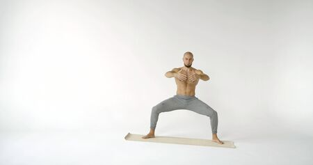 A flexible and plastic male yogi with a beard does yoga on a rug in a white Studio. He stands in the crab pose. Stockfoto