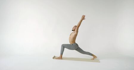 A flexible and plastic male yogi with a beard does yoga on a rug in a white Studio. He does stretching in the warrior pose of virabhadrasana.