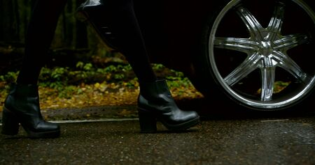 Close-up of a womans legs in black heeled shoes, she walks up to her dark classic car against a forest background.