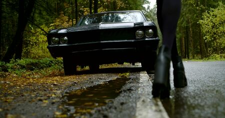 Close-up of a womans legs in black heeled shoes, black skirt and black jacket, she walks up to her dark classic car against a forest background, view from the back.