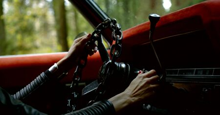 Close-up of female hands in a leather jacket holding the steering wheel of the car and start the car.