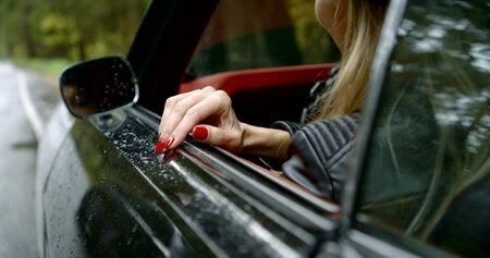 Close-up of female hands with red manicure on nails hold a wheel of the car and look out of an open window of the car. In the front mirror you can see the reflection of the girls face.