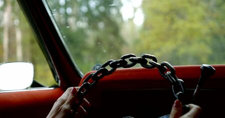 woman starts car with hands on cool chain steering wheel against green forest out of windshield slow motion close view