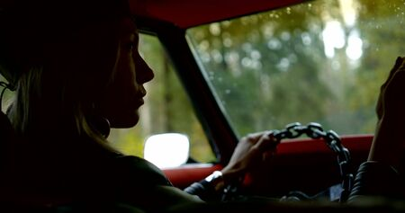 girl silhouette in leather jacket and beret puts hand on steering wheel slow motion close view from cabin 版權商用圖片