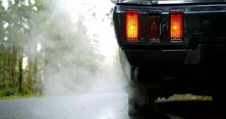 black car with lighted red tail light stands emitting white dense smoke from exhaust pipe slow motion extreme close view Zdjęcie Seryjne