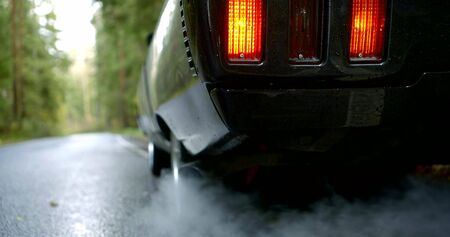 black shiny car with lighted taillights emits white smoke from exhaust pipe on wet road slow motion close view