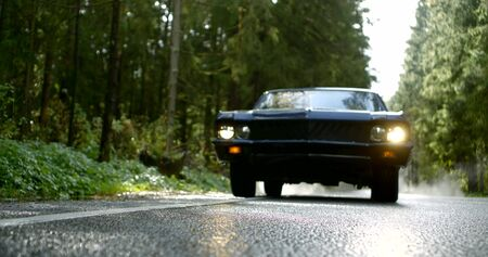 cool black sport car with lighted headlights drives forward along wet road in spring forest slow motion low angle shot