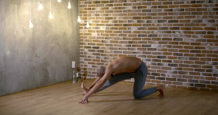 muscular bald yoga instructor stretches for Half Splits in asana against brick wall in modern light studio slow motion Zdjęcie Seryjne