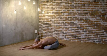 handsome yoga instructor with bare torso rests in asana on wooden floor in modern studio slow motion side view