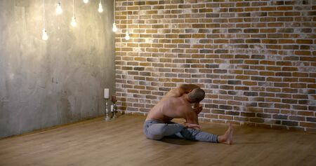 muscular yoga instructor does difficult asana Seated Three Limbed Forward Bend against red brick studio wall slow motion Zdjęcie Seryjne