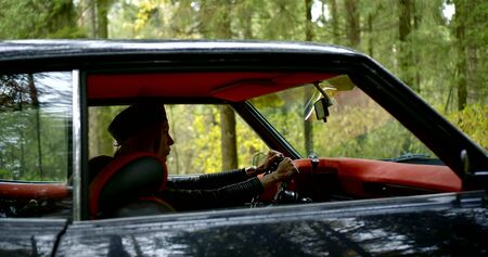 girl driver silhouette sits in black car with red interior against green forest slow motion view through window Zdjęcie Seryjne