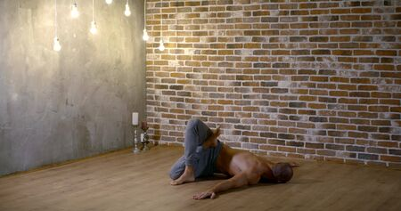handsome yoga instructor changes hard yoga asanas on wooden floor in cozy studio with hanging lamps slow motion Zdjęcie Seryjne