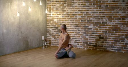 sporty bald man with bare torso sits on floor and does half lord of fishes yoga asana against brick wall slow motion