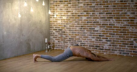 muscular bald yoga instructor stretches on floor in yoga asana Sleeping Swan against brick wall in studio slow motion