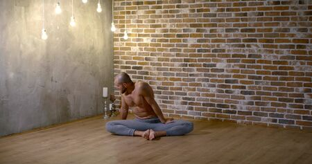 fit man in grey yoga pants sits on wooden floor and does lotus asana in cozy studio with hanging lamps slow motion Zdjęcie Seryjne