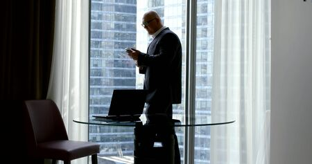 businessman is reading message in smartphone and calling, walking in office room in daytime, inside skyscraper