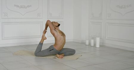 male master of yoga is performing asana on floor indoors