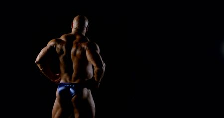 Body brutal bald muscular male bodybuilder closeup on black background, he poses, shows muscles. The view from the back.