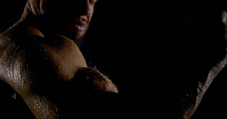 Portrait of a brutal muscular male bodybuilder close-up on a black background, he is in the rain, water is flowing down him. Shows the bicep on his arm.