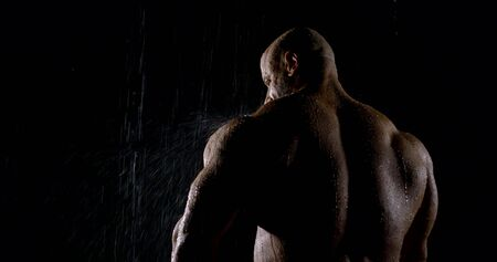 Back brutal muscular male bodybuilder close-up on a black background, he is in the rain, water flows down it.