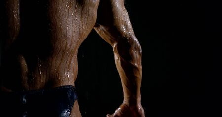 The powerful back of a brutal muscular bald male bodybuilder close-up on a black background, he is in the rain, water flows down him.