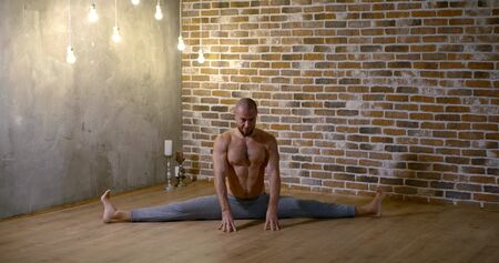 male yogi is sitting in a split on floor of room in evening and meditating with folded palms