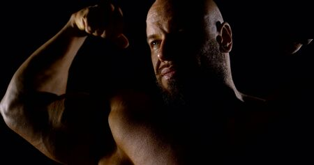 a big muscular bald bearded bodybuilder flexes his arms, strains his biceps and poses. dark key.
