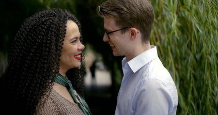 Happy beautiful girl and her successful boyfriend walking down the street. A woman in a knitted dress, a man in a white shirt and glasses. Happy happy couple family. They looked at each other Stock fotó